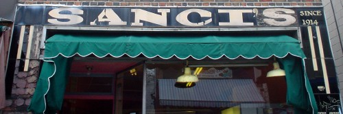 Hand-lettered sign on slate tile above awning reads SANCI'S SINCE 1914