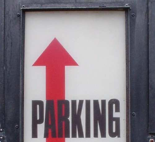 White sign has tall red uparrow and the word PARKING in black