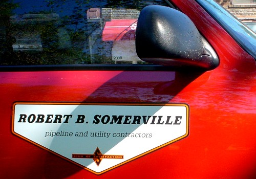 Sign on door of red truck reads ROBERT B. SOMERVILLE pipeline and utility contractors in Serifa typeface