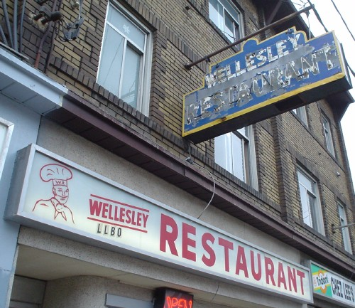 Signs on wall and hanging from pole read WELLESLEY RESTAURANT in neon, handlettered, and sansserif type