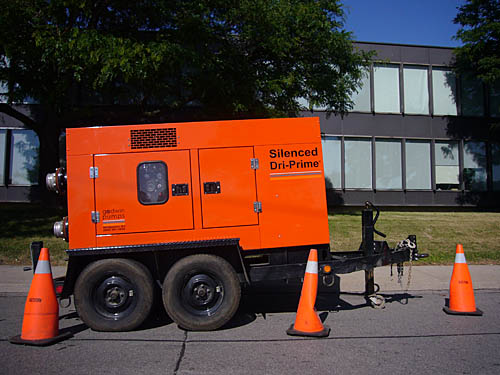 Bright-orange construction device, labelled Silenced Dri-Prime, is its own trailer and sits behind three orange pylons