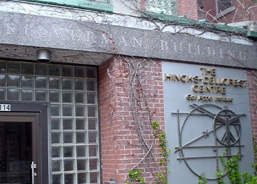 Granite plinth over glass-brick doorway reads SILVERMAN BUILDING in engraved letters. Sign on the front wall shows a Vetruvian Man illustration and THE HINCKS-DELLORES CENTRE in raised type