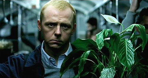 Simon Pegg stands listlessly in a subway car holding a potted plant