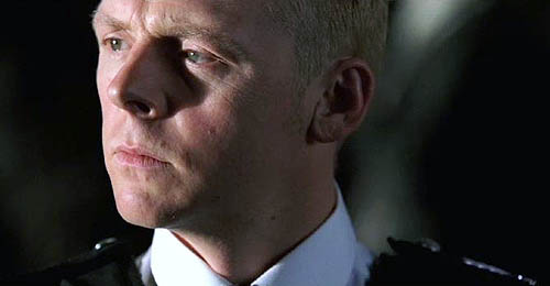 Simon Pegg, wearing police epaulets, gazes off to the side with furrowed brow