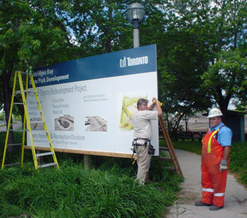 Two guys – one in safety overalls and a hard hat – install a large billboard headlined Ashbridges Bay Skate Park Devleopment
