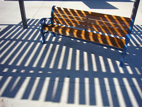Park bench has slats going one way with slat-like shadows cast the opposit eway