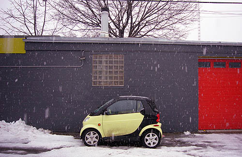With snow falling, a lime-green Smart sits parked alongside dark wall between lime-green roof trim and red garage door