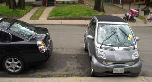 Grey Smart Fourtwo with a yellow parking ticket under its wiper sits with its nose touching the sidewalk curb