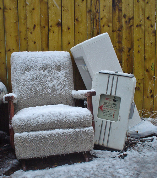 Disused armchair, water cooler, and vintage sign reading FRESH COFFEE in a display case all sit covered by wet snow