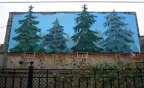 Outdoor wooden slat wall is covered with a mural of four fir trees, three of which pop out of the irregular top edge