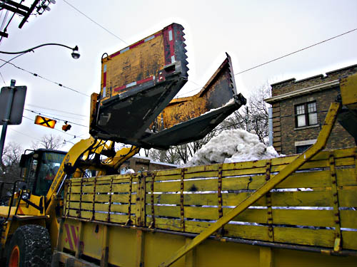 Giant claws of yellow pavement grader dump dirty snow into yellow-green dumptruck