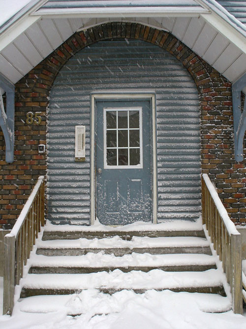 Snow-covered doorway and steps shows blue siding and '85' in metal letters on brick wall