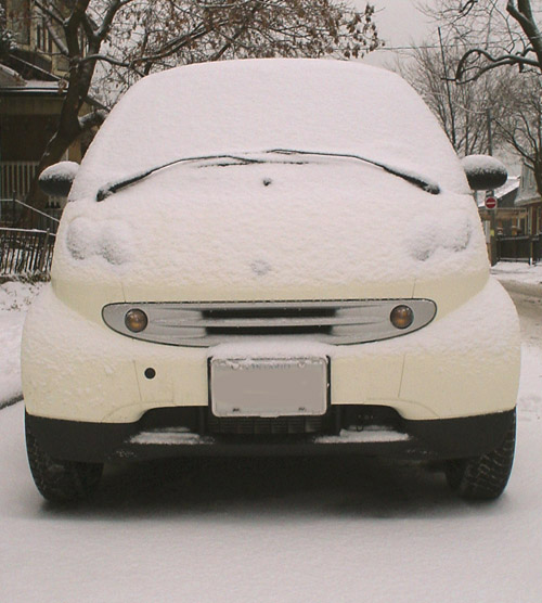 Yellow Smart Fourtwo has windscreen, hood, and headlights obscured by snow