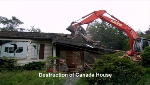 Front-end loader pulls apart the roof of a house. 'Destruction of Canada House'
