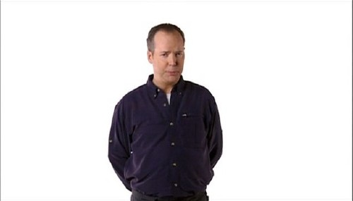 Against a blinding white screen, Coupland stands, arms behind his back, in a blue shirt with white buttons