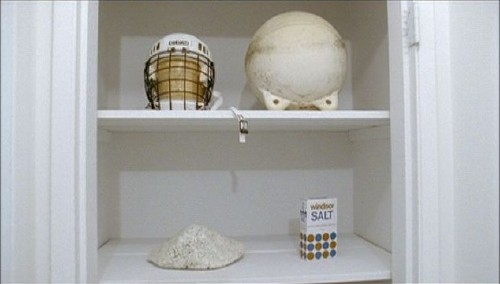 White shelves inset in white wall contain a white hockey helmet, some kind of white ball, a white Windsor Salt box, and some kind of white mound