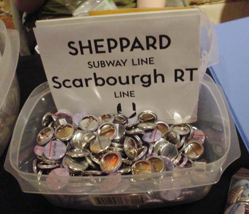Plastic bin is filled with small pin-on buttons and includes a sign reading SHEPPARD SUBWAY LINE Scarborough RT LINE