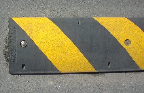 Bolted to the pavement, a yellow-and-black-striped speed bump is engraved 'Easy Rider' at the tip