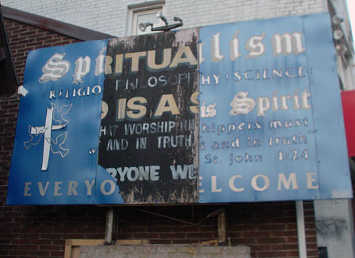 Two layers of billboard for SPIRITUALISM RELIGION PHILOSOPHY · SCIENCE	 show through, with a blue strip on left and right sides and a black strip in the middle