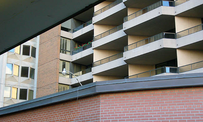 View through balcony overhang shows brick wall, staggered concrete balconies, and diamond-like concrete window surrounds of other buildings