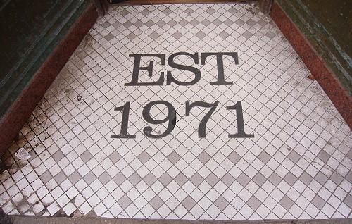 Terrazzo entranceway reads EST 1971
