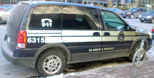 Navy-blue minivan has brigh reflective stripes and markings (6315, 9·1·1, TO SERVE AND PROTECT)