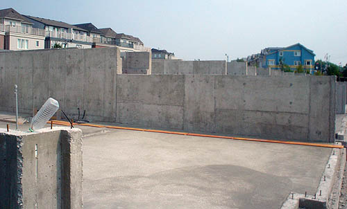 Grey concrete walls demarcate the edges of adjacent plots of land in a subdivision