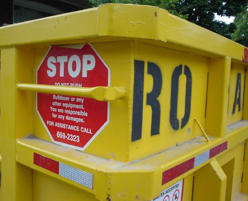 Bright yellow dumpster bears a stop sign and stenciled letters RO