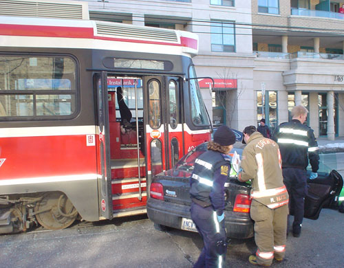Red streetcar has its door open as it lodges against the left side of a blue car. Uniformed firefighters and paramedics work at the scene