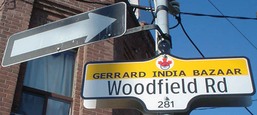 One-way arrow stands on same pole as sign reading Woodfield Rd. in Clearview and GERRARD INDIA BAZAAR in Verdana