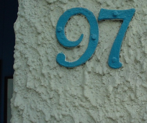 Blue house signs nailed to white stucco wall read '97'