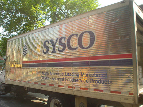 Mirror-like metal truck body is labelled SYSCO in Palatino Bold