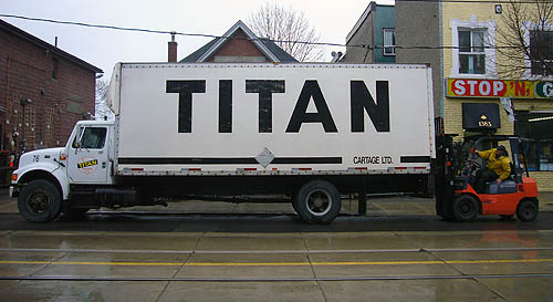 Large transport truck, emblazoned TITAN, is parked on a rainy street. A guy in a forklift drives up behind it