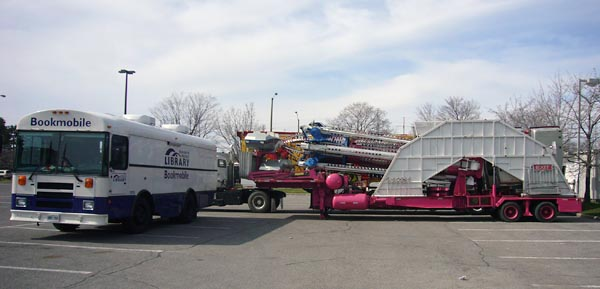 Bookmobile parked alongside and pointing away from a set of folded silver-and-blue booms on a hot-pink trailer