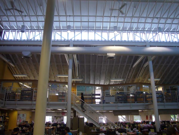 Mezzanine below a ceiling with side-facing skylights, white pipes that look like ribs, and ceiling fans