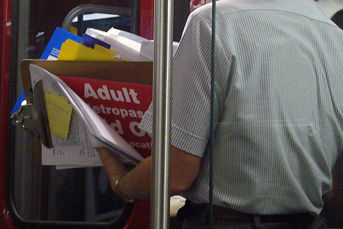 Person in striped shirt, seen from neck to waist, holds clipboard with a visible sign amid the papers: Adult etropass
