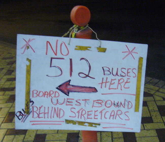 Handwritten sign on pylon reads * NO 512 BUSES HERE * and more