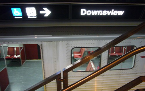 Sign over parked subway car has blurry pictographs and less-legible word Downsview