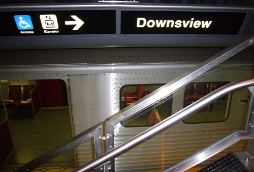Sign over parked subway car has two pictographs, an arrow, and the word Downsview