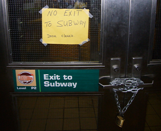 Sign on door: Exit to subway. Scrawled sign taped to window: NO EXIT TO SUBWAY DOOR CLOSED