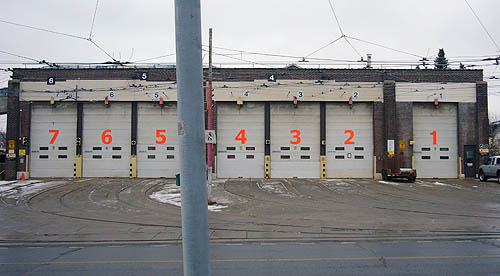 Huge doors of a streetcar garage are numbered 7 through 1 in fluorescent orange Frutiger