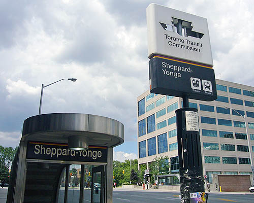 Entrance has massive semicircular steel canopy and reads Sheppard-Yonge. Nearby standing sign has missing TTC logos, through which clouds are visible