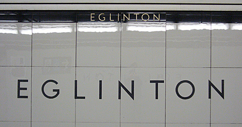 Lightweight black letters on very large glossy grey tiles read EGLINTON