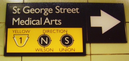 Sign reads St George Street Medical Arts in Gill, with yellow icons and direction indicators below also in Gill