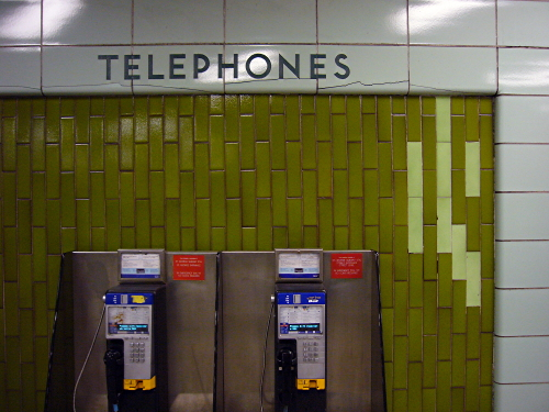 Slightly cracked green tile walls inscribed with TELEPHONES (above two modern payphones)