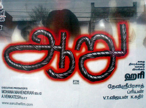 Tamil-language sign has giant black display type that looks like twisted liquorice, with each stroke surrounded by a red shadow
