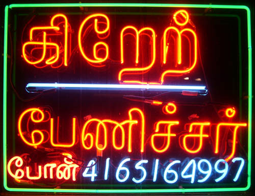 Neon sign has two lines of orange Tamil lettering divided by a white line, then more Tamil and the number 4165164997