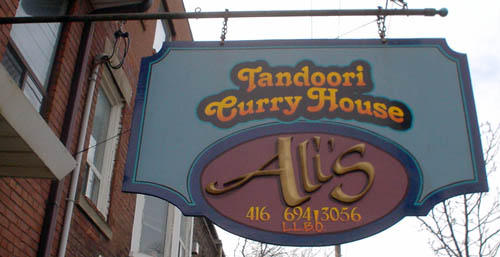 Hanging sign reads Tandoori Curry House, in letters coloured like a sunset, surrounding the word Ali's and a phone number