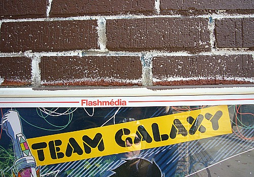 Top of banner inside Flashmédia frame and below a brick wall reads TEAM GALAXY in stencil letters