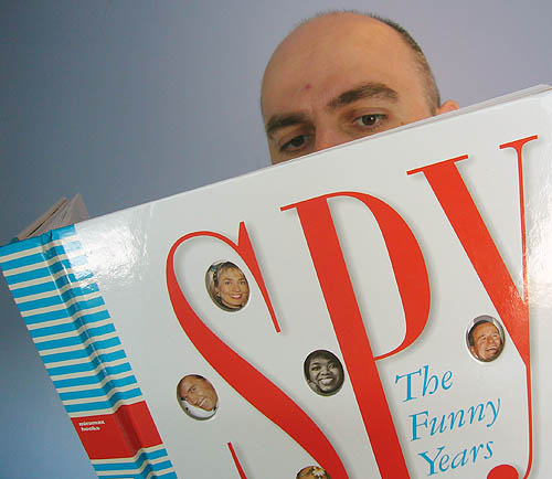 """I hold up and peer into the book '""""Spy"""": The Funny Years'"""